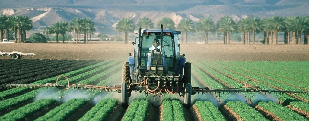 传统的农民开车驶过拖拉机喷洒的田地